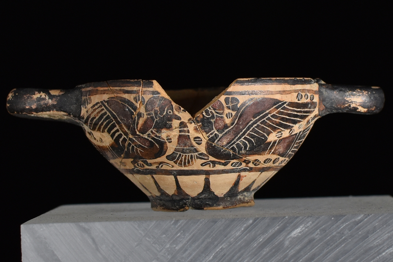 Bowl w convex sides spreading from low offset base to plain rim, prominent nipple on int center; horizontal handles of rounded rectangular section.attached at either side at rim.  Main zone of decoration defined by 2 h stripes above, one below filled w opposing sphinxes on opposite sides of inverted palmette w small blob rosettes in main fields, larger under handles, all decorated w fine incised detail; below rays rise from base which solidly coated on ext w paint continuing onto to underside of base; handles solidly coated on ext.; int thinly coated w paint of varying thickness, so as to produce h stripes.