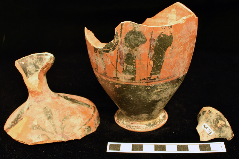Flaring mouth lekythos w lip coated inside & out, lower body & foot, exclusive of edge, & ext & sides of handle coated; main field on body bordered by narrow stripe above & below.  On shoulder: 7-petalled palmette opposite handle v palmette flanked by men in profile in himatia.  On body: