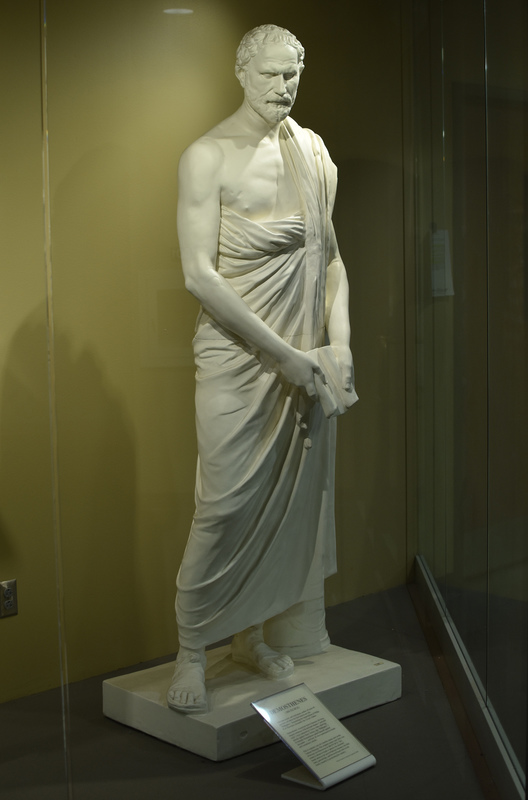 """Modern plaster replica of Roman marble copy of the Greek bronze original by the sculptor Polyeuktos, dating ca. 280 BCE. Perhaps the most well-known of the Greek orators, Demosthenes is said to have overcome his stuttering speech by speaking with pebbles in his mouth against the roar of the sea. A writer of speeches for the courts, Demosthenes was a passionate defender of his native Athens and in a series of speeches known as the """"Philippics"""" he urged his fellow-citizens to withstand the advances of Philip of Macedon, father of Alexander the Great. Over 50 Roman copies of the work are known; the original of ours is in the Vatican Museums in Rome."""