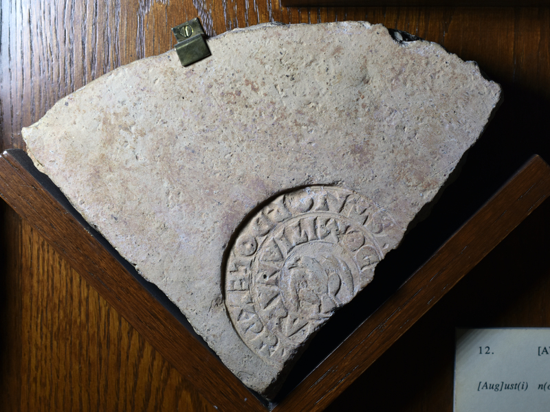 Fragment w contour of equilateral triangle, one leg convex. Large circular stamp w eagle facing l in center and around it in two rows of quadrate letters: USTINOPDOLEXPRL/DOMITIANARUM...S for AUGUST NOSTRI OPUS DOLIARE EX PRAEDIS LUCILLAE/DOMITIANARUM...S