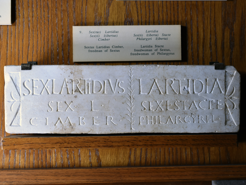Plain plaque of white marble with decorated left & right margins; the 2 sets of inscriptions separated by a branch.