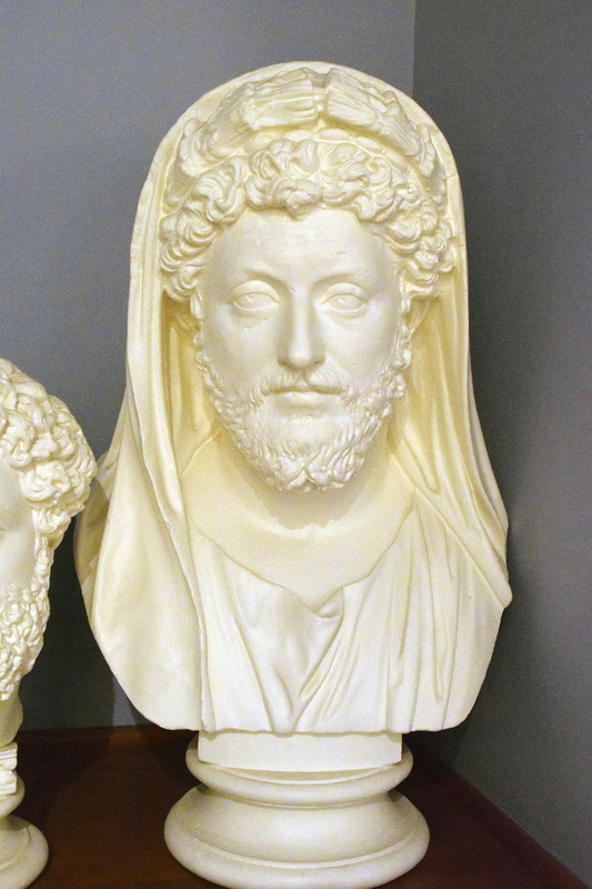 """Marcus Aurelius, one of ancient Rome's most notable emperors, was born in 121.  Marcus was introduced to politics at an early age, with his grandfather serving as consul for the third time in 126. His family was also close to the emperor Hadrian, and Marcus was known as one of Hadrian's favorites.  These valuable connections to the imperial family paid off when Marcus became quaestor in 139, and finally consul in both 140 and145.  His reign as emperor did not begin until 161, and lasted eighteen years.  Although the empire was not at peace during most of his reign, (there were problems in Britian, Upper Germany, and other places throughout the region), Marcus was not remembered for his military accomplisments.  Instead he is better known for his philisophical musings, especially in a work entitled Meditiations, a journal in which, """"he recorded (in Greek) his own reflections on human life and the ways of the gods,"""" (Hornblower and Spawforth 220).   The portraiture of Marcus Aurelius differs from that of preceeding emperors, in that it not only shows his physial characteristics at each stage in his life, but also attempts to reflect the emperor's psychological state.  As a teenager, Marcus' youthful facial features included """"oval-shaped eyes, a strong nose, highly arched brows, and a beautiful rounded mouth"""" (Kleiner 270).  His tousled hair, smooth skin, and half-closed eyelids are also trademarks of his portraiture.  Over time however, Marcus is depicted with a moustache and beard and, near the end of his career he wears a, """"long and full beard that is divided in the center and arranged in individual parallel locks"""" (Kleiner 273). In this particular bust at the Wilcox collection, Marcus is depicted as approximately forty-years-old with droopy eyes, a full beard and moustache, and scattered lines upon his forehead.  The Wilcox collection houses a copy of a portrait bust of Marcus Aurelius that is currently displayed in the British Museum in London."""