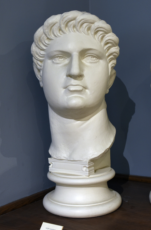 """Cast based on an original in the British Museum. Nero Claudius Caesar, born in Antium in 37 to Gnaeus Domitius Ahenobarbus and Agrippina the Younger, was one of Rome's most intriguing emperors. His mother was the fourth wife of the emperor Claudius and she persuaded him to adopt her son Nero. Agrippina's malicious intentions were to kill Claudius so that her son would attain the position of emperor, so upon Claudius' untimely death, seventeen-year-old Nero ascended to the throne in the year 54.  Nero's personal accomplishments were numerous: he played the lyre, sang, recited his own poetry, competed in the Olympic games, and enjoyed painting and sculpture. Nero is most remembered by the quote, """"Nero fiddled while Rome burned,"""" which may hold some truth. Apparently after a devastating fire ravaged the city of Rome in 64, Nero took the opportunity to displace citizens and build a grand palace for himself called the Domus Aurea in the center of the city. By this time Nero was out of control, and in 65, many high ranking Romans planned the Pisonian conspiracy: a plot to assassinate Nero and name Gaius Calpurnius Piso as the new emperor. Nero unfortunately discovered their plans and put many people to death including his tutor Seneca. Many people died at the hands of Nero throughout his reign including his wife Poppaea, his mother Agrippina, and countless others. The extremely unpopular emperor eventually died at the age of thirty-two after committing suicide in the year 68, """"reputedly lamenting, 'What an artist dies with me!"""" (Hornblower and Spawforth, 1038).  Nero's portraiture is rather hard to study chronologically since so many of his portraits were destroyed or defaced after his death. Many coins have survived that show Nero as the emperor, but less then 25 sculptures remain and most of them depict Nero in his youth. His physical characteristics include, """"high cheekbones, fleshy jaw and neck, and a full head of tousled hair that is brushed from the crown of his hea"""