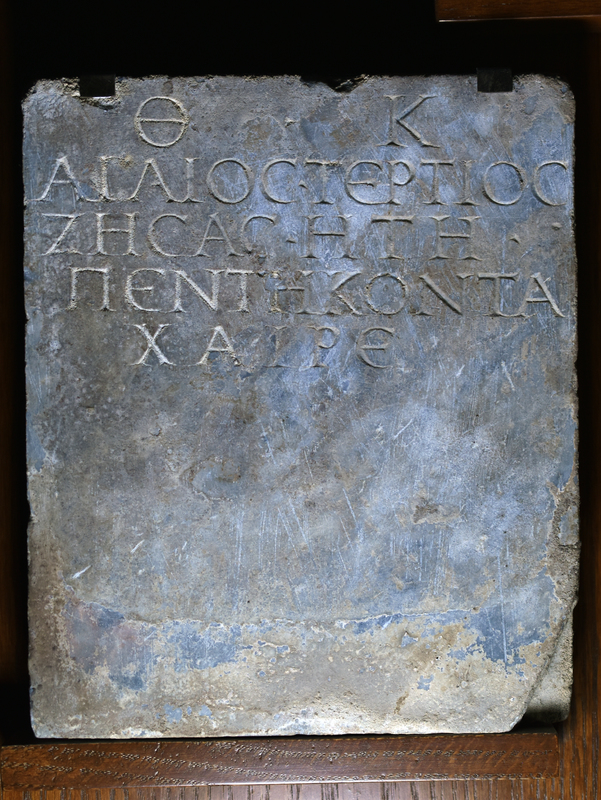 Rectangular slab w inscription in capital letters in 5 lines:  Θ • Κ  ΑΓΑΙΟΣ ΤΕΡΤΙΟΣ ΖΗΣΑΣ ΗΤΗ ΠΕΝΤΕΚΟΝΤΑ ΧΑΙΡΕ  To the gods of the underworld (θεοῖς καταχθονίοις / theois katakhthoniois) Agaios Tertios having lived 50 years Greetings!  Only face well smoothed, back rough pecked, edges incompletely ground.