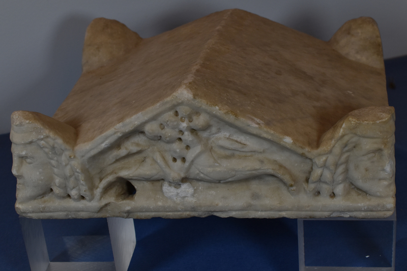Lid in the form of gabled roof with 4 projecting acroteria at corners.  On primary façade gable filled with two cornucopiae in relief and acroteria carved as dramatic masks: heads, ? male, with crown-like headdress from which 3 long curls extend to frame face on either side; articulation of eyes, nose and mouth.  Gabled surface opposite and acroteria uncarved as are sides and surfaces of gable.