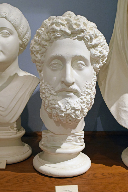 """Cast based on original portrait in the British Museum, London. Born while his father, Marcus Aurelius, was emperor, Commodus co-ruled with him (177-180) before reigning solely (180-193). His reign was fairly peaceful but marked by the emperor's rising megalomania. Declaring himself a new Hercules (many statues of him refer to this), he began fighting in the arena as a gladiator. In November 192, he was assassinated.   Lucius Aurelius Commodus, son of Marcus Aurelius and Annia Galeria Faustina, was born in August of 161.  One of the only emperors """"born in the purple,"""" or from the reigning emperor, (most were adopted by their predecessors), he assumed control of Rome March 17, 180, upon Marcus Aurelius' death.  During his reign, major wars were avoided, with the exception of an uprising in Britian and some minor disturbances along the Danube.  However, there was little peace in the city of Rome with Commodus in charge.  This tyrannical ruler is described as, """"quite fierce with sexual desire and greed, with cruelty, faithful to no one..."""" (Banchich 15).  There was a thwarted assassination attempt in 182, which implicated the emperor's sister and many others, but their plans were foiled and many were killed at the hands of Commdus.  By this time Commodus, who was, """"obsessively devoted to performing as a gladiator, [and] appeared to be dangerously deranged,"""" (Hornblower and Spawforth 374).  Commodus' assassination attempts were many, even his favorite concubine Marcia tried to kill him by offering him a drink of poison after bathing, but his end finally come when he was strangled on the night of December 31, 192 by a wrestling instructor.  Most portraiture depicts Commodus as having, """"[a] long, oval face, arched brows, and half-closed eyes, large nose, small mouth, and arrogant expression.  His high forehead is crowned with a halo of tousled hair that is deeply drilled, and he wears a plastically tendered full beard,"""" (Kleiner 277).  The artists of Commodus' portraits, l"""