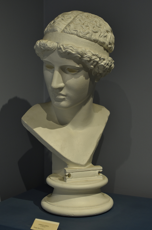 """The original acrolithic statue was created by Pheidias (ca. 440-435) and paid for by Athenians living on the island of Lemnos (hence, the """"Lemnian Athena""""); the statue stood on the Acropolis in Athens. The Wilcox Collection has a plaster cast replica of one of the two existing Roman marble copies. The Roman copies, a head preserved in Museo Civico, Bologna, and a body that is shown in the Staatliche Museum, Dresden, were modeled after an original Greek bronze. Adolf Furtwängler reconstructed the statue in 1891. His reconstruction is in Dresden. There is also a well-preserved cast of the whole figure in Oxford, England. The association of the head and body has been disputed, and Athena is also missing her arms. It is presumed that she held either an owl or a helmet in her outstretched arms. The original sculpture was among the first of many famous works to come, including Athena Parthenos at Athens and the Zeus in the temple of Olympia. It was said by the ancient Pausanias that the Athena Lemnia is the most worth seeing of the works of Pheidias."""