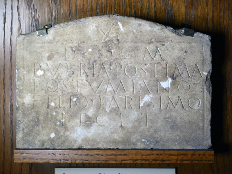 Plain plaque of white marble with border; in the pediment, a small stone-mason's dolabra, pick.